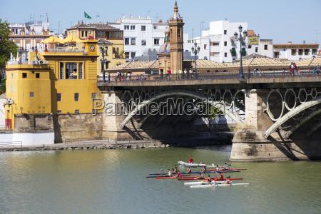 kayakers passing under the triana bridge
