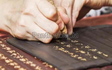 woman carving inscriptions on wooden panels