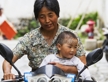 chinese, woman, and, boy, riding, a - 25401602