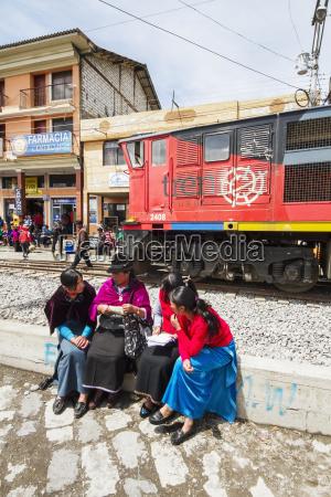 ecuadorian women sitting by the railway