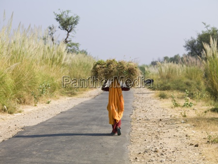 woman carrying bale of hay on