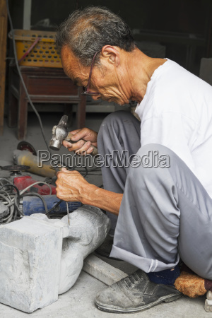 craftsman carving a stone lion xidi