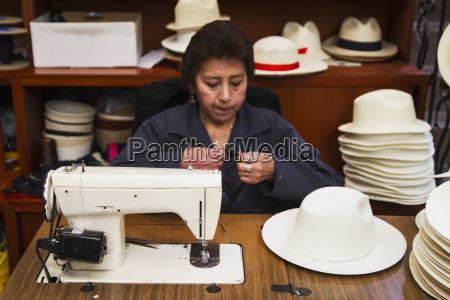 woman sewing the black brim on