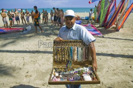 man selling perlenhalsketten am strand mit