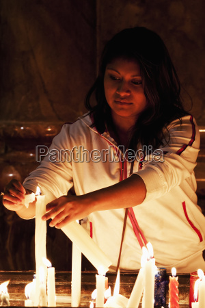 woman lighting candles at the catedral