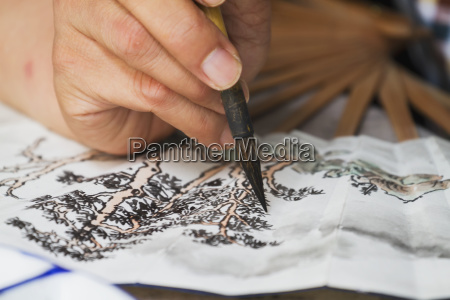 artist painting a fan with a