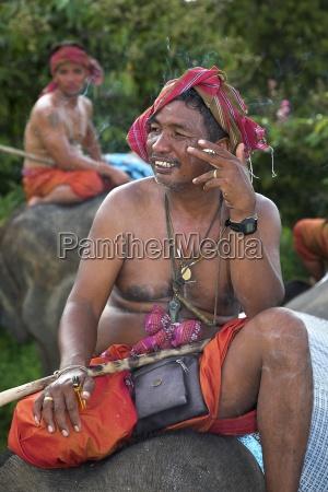 men sitting on elephants isan thailand