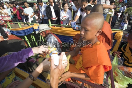buddhist monks on elephant getting offerings