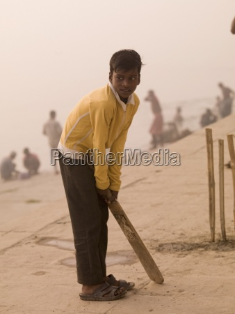 young boy playing cricket by the