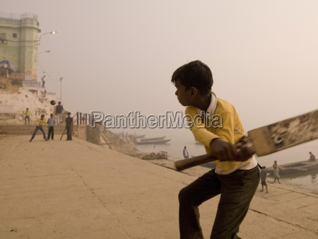 young boys playing cricket by the