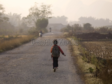 young boy skipping down a road