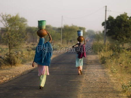 women carrying buckets and bowls in