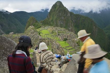 tourist group descending steps machu picchu