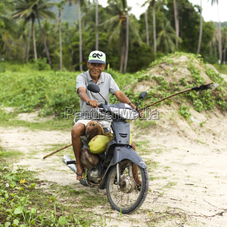 a thai man carrying coconuts on