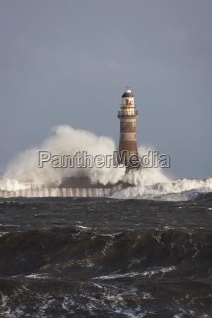 waves crashing against a lighthouse sunderland