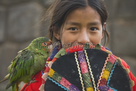 girl in traditional clothing with parrot