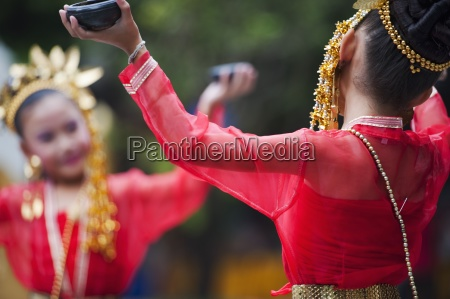 young thai girls perform traditional dance