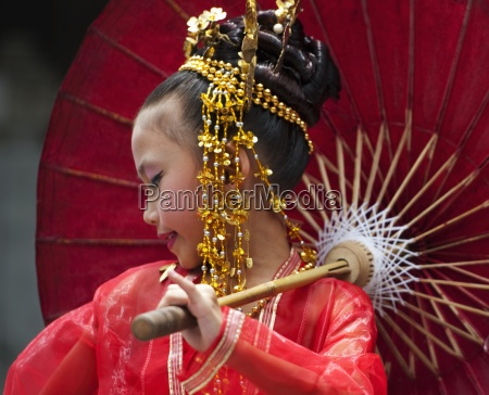 young thai girl performs traditional dance