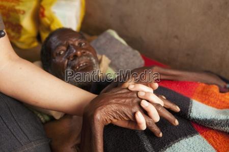 eine krankenschwester haelt die hand eines