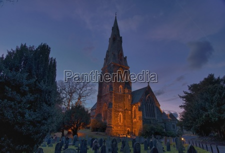 a cemetery and church building illuminated