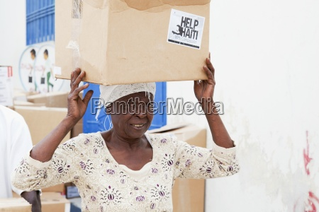 a woman carries a box of