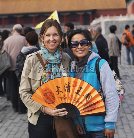 two female tourists with a fan