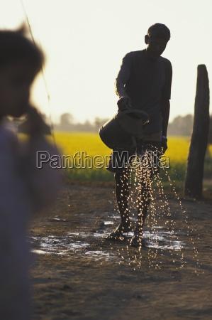 man watering ground sauhara chitwan nepal