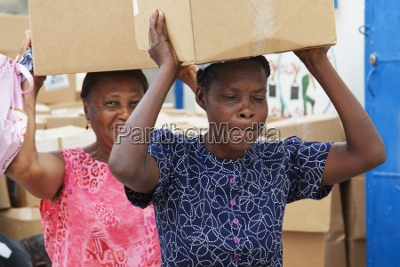 women carrying boxes on their head