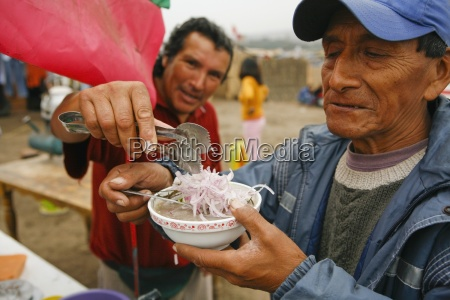 man being served soup lima peru