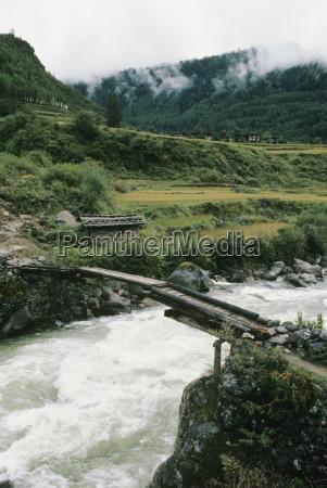 bhutan wooden bridge over rushing river
