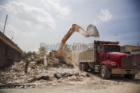 a backhoe clears rubble into a