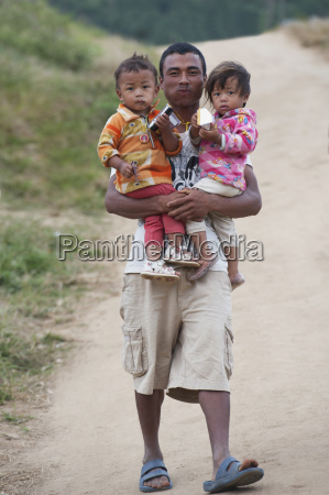bhutanese man holding two children punakha