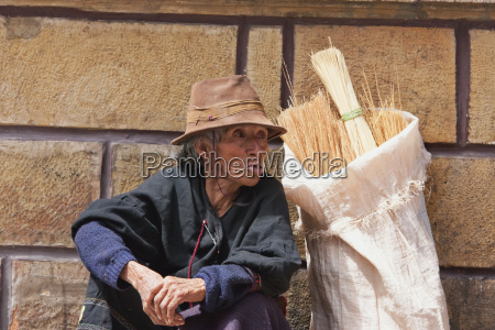 broom vendor sitting against wall sucre