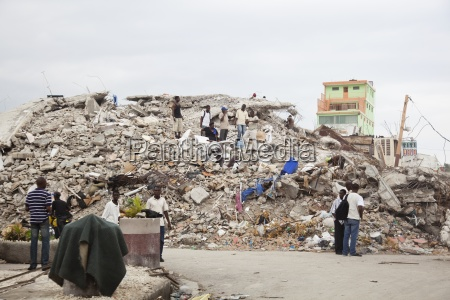 haitian people standing amongst the ruins