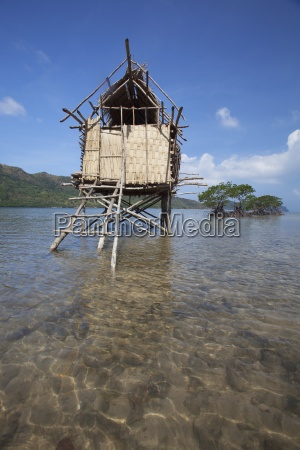 a small thatched stilt house sits