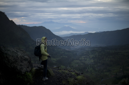 woman overlooking a valley with volcanos