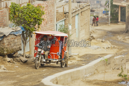 a cycle rickshaw coming up a
