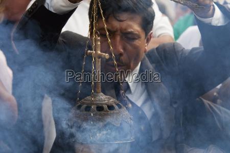 man waiving an incense burner during