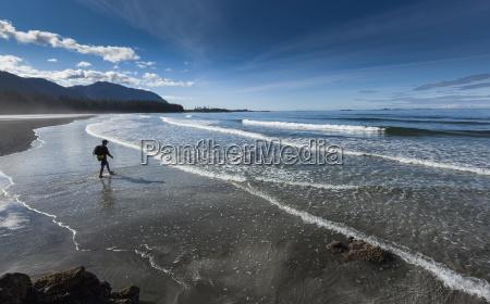 a man walks along the sandy