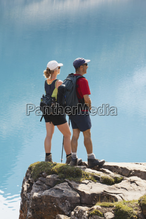 female and male hikers on rock