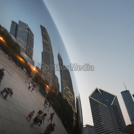 reflection of skyscrapers and pedestrians in
