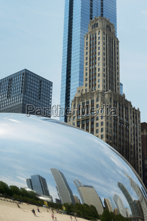 rounded silver sculpture reflecting pedestrians and