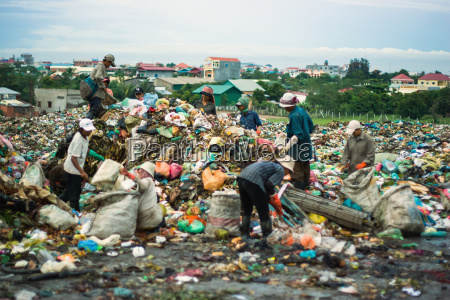 cambodia people looking through dumped trash