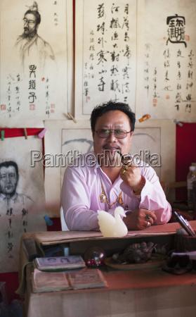 thailand man smoking pipe while sitting