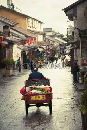 woman rides tricycle with vegetables on