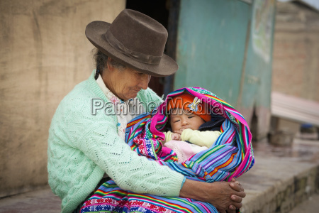 a woman holds a baby wrapped