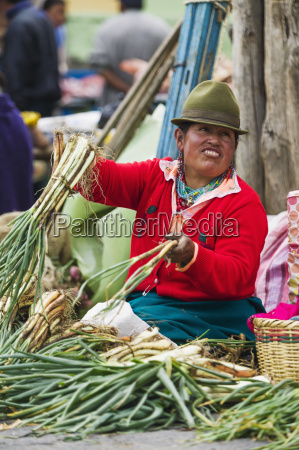 a woman selling vegetables at saquisili