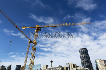 construction cranes with calgary cityscape in