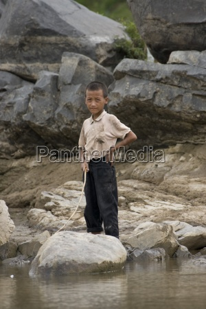child standing on the banks of