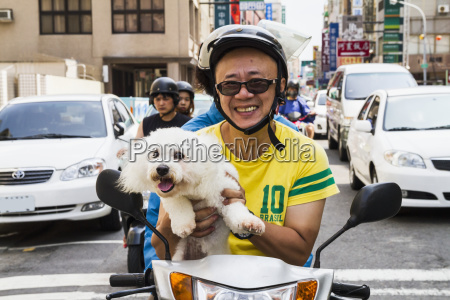man carrying a poodle on his